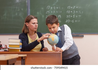 Teacher and boy student with a globe at school.