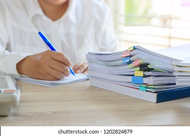 Teacher is checking student homework assignment and report on desk in school for score. Unfinished paperwork stacked in archive with color papers and paper clips. Education and business concept.