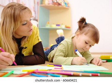 Teacher and child draw with felt-tip pens in preschool
