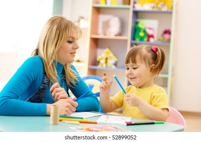 Teacher and child draw with markers in preschool