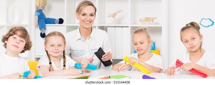 Teacher and children during art class at school