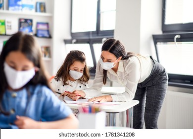 Teacher and children with face mask back at school after covid-19 quarantine and lockdown. - Shutterstock ID 1781341208