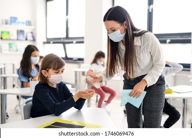 Teacher, children with face mask at school after covid-19 quarantine and lockdown.