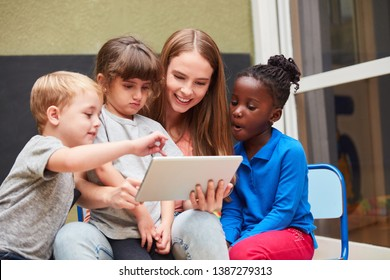 Teacher and children have fun learning with a tablet computer in the day care center