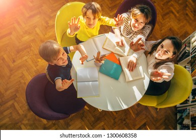 Teacher and children looking up at camera while sitting in a circle round table at library. Top view of librarian sitting with four children. Teacher reading book to girl and boys at school