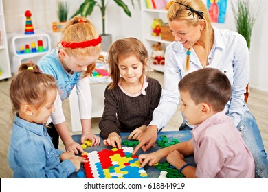 Teacher and children are playing a board game in the classroom.