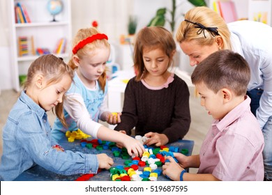 Teacher and children are playing with puzzle in the classroom