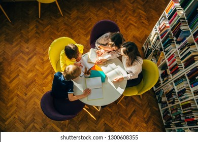 Teacher and children reading fairy tales while sitting in a circle round table at library.Top view of librarian sitting with three multiethnic children. Teacher reading book to girl and boys at school
