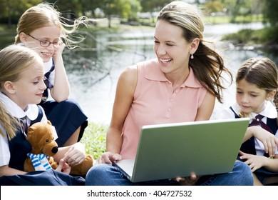 A teacher and children using a laptop outside