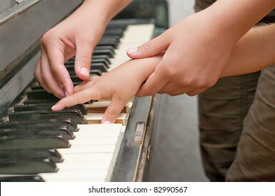 teacher and child's hands touch keyboard