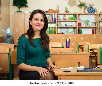 teacher in classroom near desks