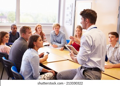 Teacher With College Students Giving Lesson In Classroom