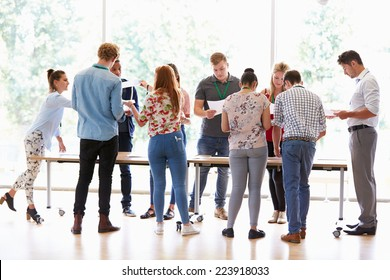 Teacher With College Students Standing By Desks In Classroom