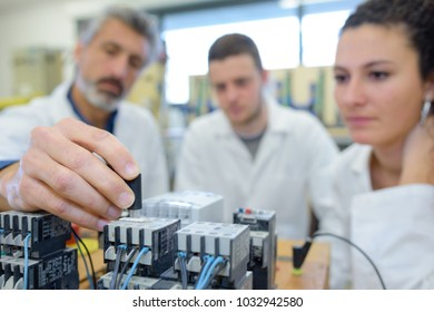 teacher connecting electronics circuit as students look on