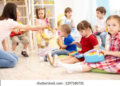 Teacher and cute children during music lesson in preschool