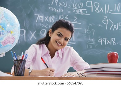 teacher at desk, smiling at camera (horizontal)