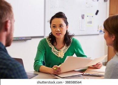 Teacher at desk talking to adult education students