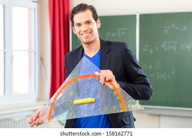 Teacher or docent in school holding a geometry triangle in front of a blackboard in school class