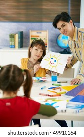Teacher and elementary age schoolgirl showing colorful paining to classmate in art class in primary school classroom.