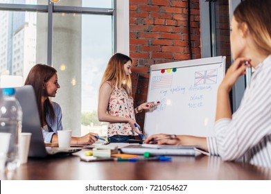 Teacher explaining differences between American and British spelling writing on whiteboard while adult students sitting at desk listening to her in stylish English language school