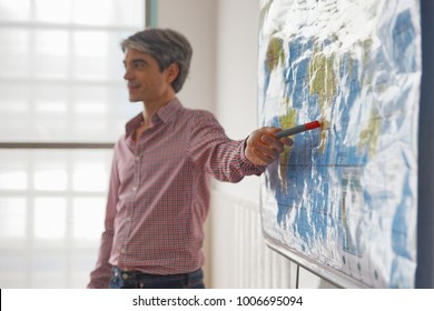 Teacher explaining geographic map in a classroom.