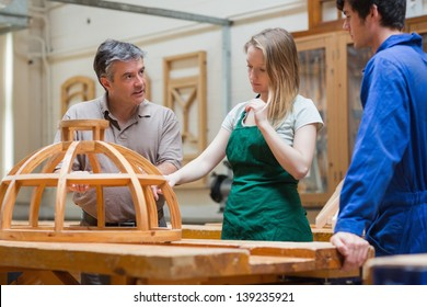 Teacher explaining a structure to two students who are standing in a woodwork class