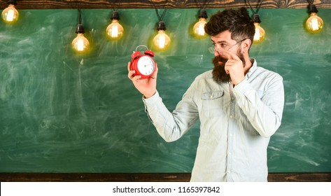 Teacher in eyeglasses holds alarm clock. Schedule and regime concept. Man with beard and mustache on concentrated face in classroom. Bearded hipster holds clock, chalkboard on background, copy space.