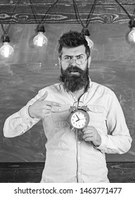 Teacher in eyeglasses holds alarm clock. Schedule and regime concept. Bearded hipster holds clock, chalkboard on background, copy space. Man with beard and mustache on surprised face pointing at clock