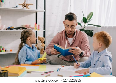 teacher in eyeglasses reading book to kids at table in classroom