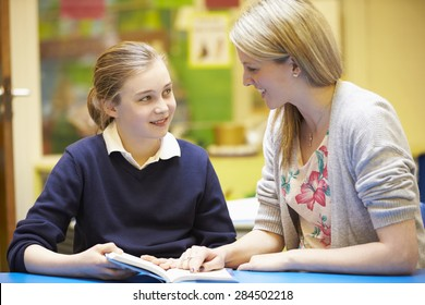 Teacher With Female Pupil Reading At Desk In Classroom