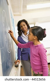 Teacher and female student at the blackboard with clock drawing on it.