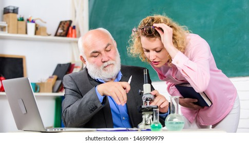 Teacher and girl with notepad near chalkboard. Biology science. Study biology. College university education. Biologist or chemist with microscope teaching student biology. Biological research.