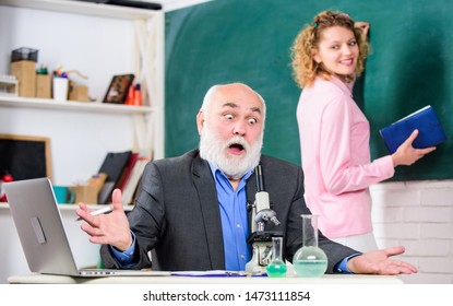 Teacher and girl with notepad near chalkboard. College university education. Biologist or chemist with microscope teaching student biology. Biology science. Study biology. Biological research.