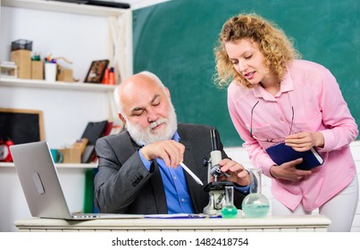 Teacher and girl with notepad near chalkboard. Biology science. Study biology. Biological research. College university education. Biologist or chemist with microscope teaching student biology.
