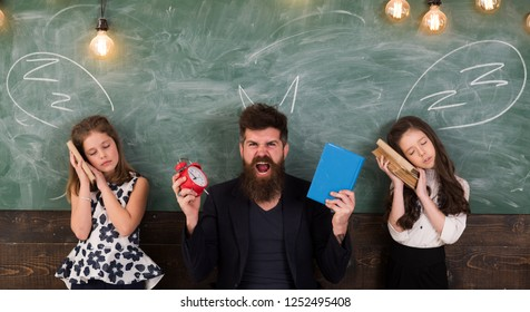 Teacher and girls pupils in classroom, chalkboard on background. Children and teacher with drawn by chalk horns. Horrible lesson concept. Man with beard shouting while schoolgirls pretend sleeping
