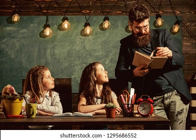 Teacher and girls pupils in classroom, chalkboard on background. Curious cheerful children listening teacher with attention. Primary school concept. Man with beard teaches schoolgirls, reading book