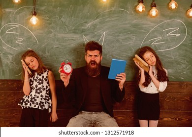 Teacher and girls pupils in classroom, chalkboard on background. Children and teacher with drawn by chalk horns. Man with beard shouting while schoolgirls pretend sleeping. Horrible lesson concept