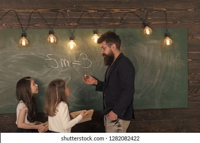 Teacher and girls pupils in classroom near chalkboard. Man with beard in formal suit teaches schoolgirls physics. Curious concentrated children listening teacher with attention. Physics lesson .