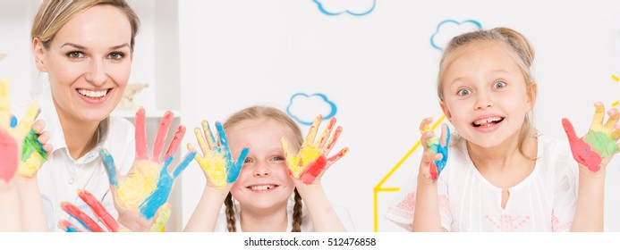 Teacher and girls showing color painted hands