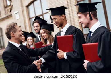 The teacher gives the students diplomas in the courtyard of the university. They finish their studies at the university. He graduates.