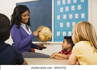 Teacher giving geography lesson in school classroom with globe.