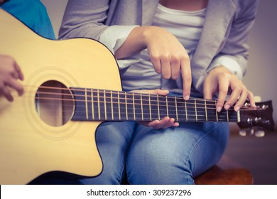 Teacher giving guitar lessons to pupil in a classroom