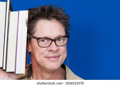 Teacher with glasses, happy with books in hand showing people