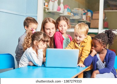 Teacher and group of children learning together at laptop computer in elementary school