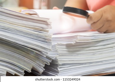 Teacher hand holding magnifier is searching for student's homework assignment on table in office to make a check and inspect. Stack of unfinished paperwork and reports. Education and business concept.