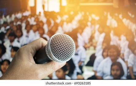 teacher hand holding microphone for speech and teaching  at meeting room, conference hall in school and college, selective focus, education concept
