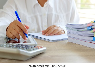 Teacher hand is holding pen for checking student homework assignments on desk in school. Unfinished paperwork stacked in archive with color papers and paper clips. Education and business concept.