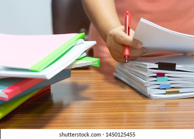 Teacher hand holding red pen for checking students homework assignment and pile of unfinished paperwork stacked in archive with colorful plastic slide binder bar beside. Business and education concept