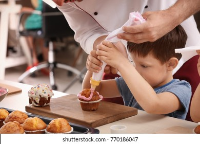 Teacher helping boy to decorate cupcake during cooking classes