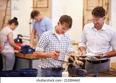 Teacher Helping College Students Studying Plumbing